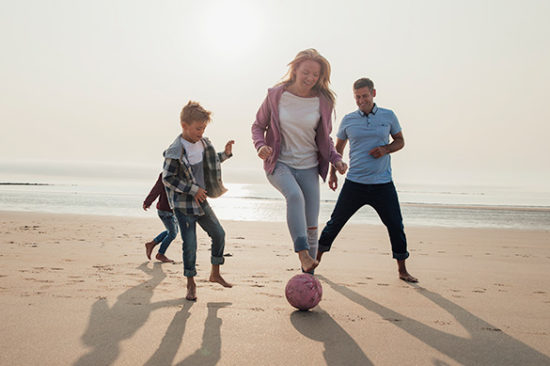 Active Iron family on the beach kicking a ball about